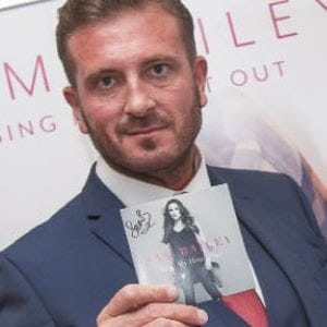 Man holds up signed Sam Bailey Album Cover